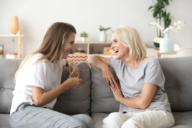 Смеяться жизнерадостной старой матери и молодой взрослой дочери говоря к стоковое фото