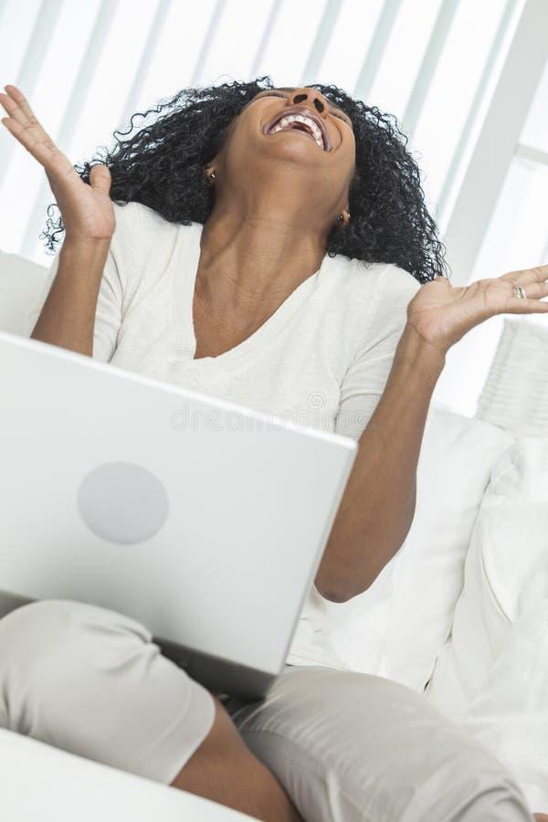 Смеяться над портативного компьютера женщины афроамериканца стоковые изображения rf
