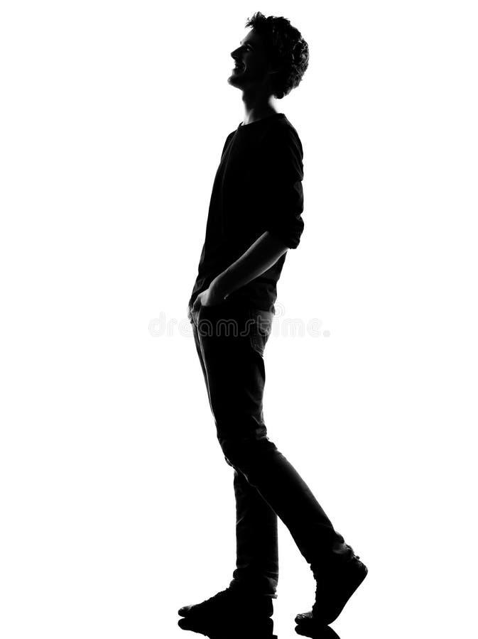 Смеяться над силуэта молодого человека гуляя счастливый стоковые фотографии rf