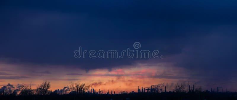 Смог над промышленным городом на заходе солнца стоковые изображения