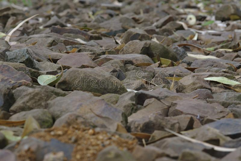 Смолотый поверхностный путь сделал вне камешки и камни стоковые фото