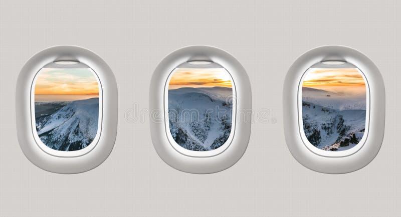 Смотреть вне окна самолета к горам зимы стоковое изображение