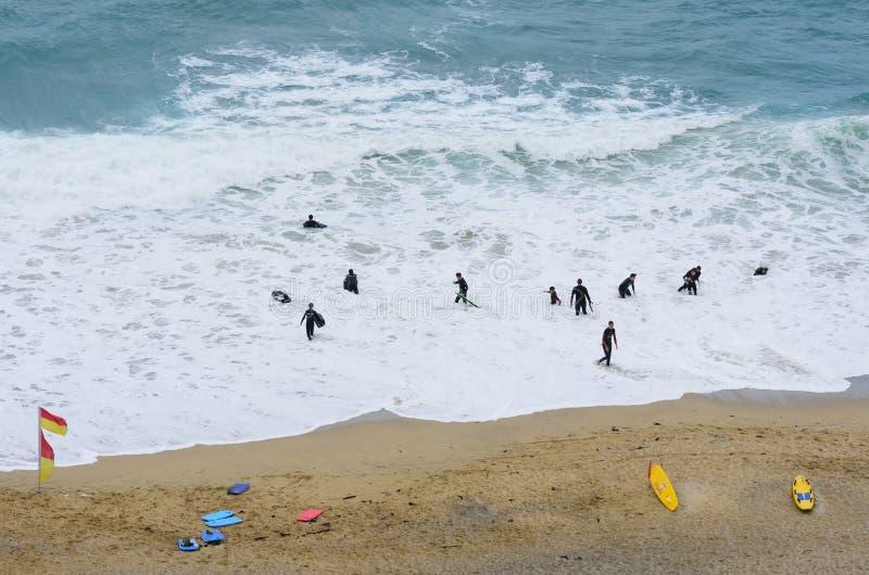 Смотреть вниз на группе в составе серферы в мокрых одеждах на пляже стоковое фото