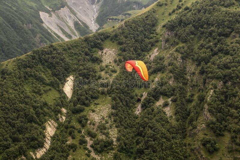 Смотреть вниз на скользить вида пар высоким над более низкими горами Кавказ со скалами и деревьями и крошечным рекой бежать далек стоковые фотографии rf