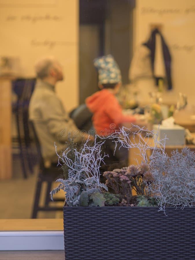Смотреть внутри к мальчику окна кофейни хлебопекарни молодому и его отцу стоковое изображение rf