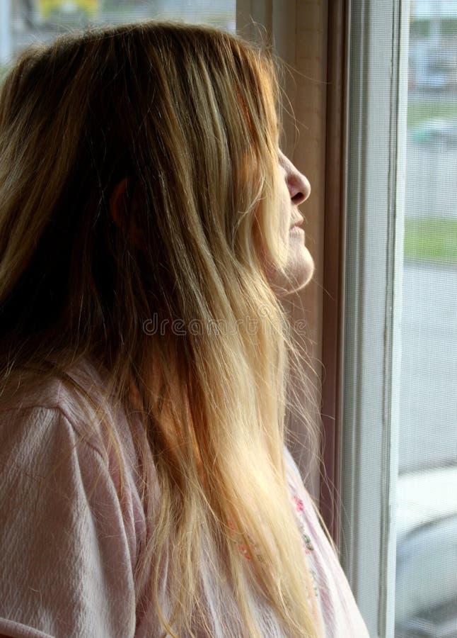 смотреть женщину окна стоковая фотография rf
