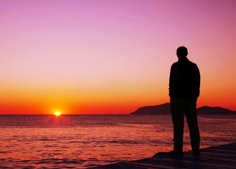 смотреть заход солнца человека стоковое фото