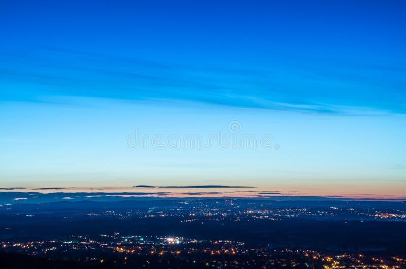 Смотреть через смесь сельской местности и городков разбросанных с уличными светами только перед восходом солнца Смотреть вниз от стоковые изображения rf