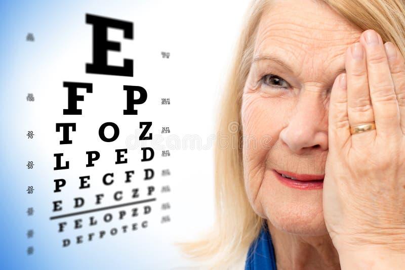 Смотрите на съемку старшей женщины с диаграммой испытания зрения стоковая фотография rf