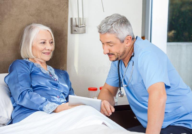 Смотритель и старшая женщина используя ПК таблетки стоковые изображения