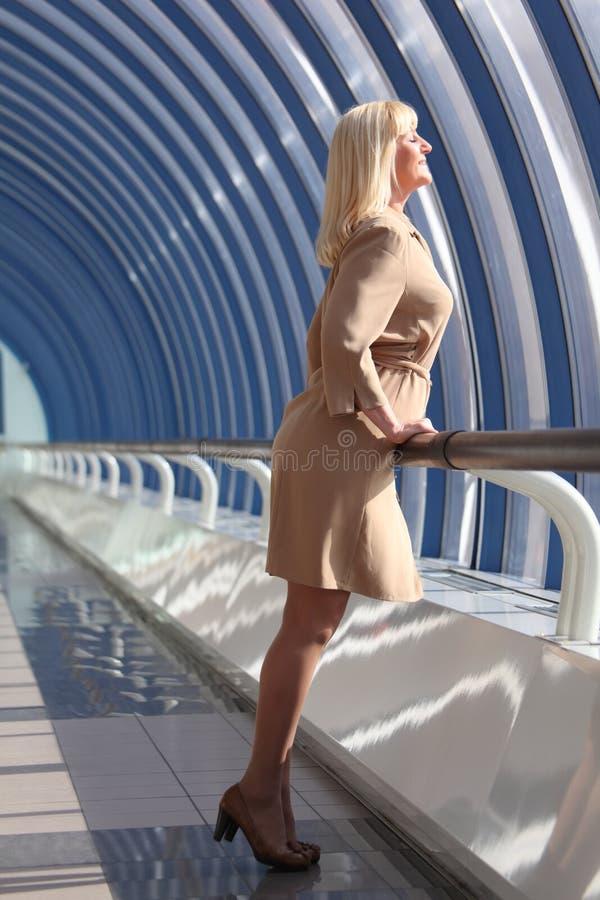 смотрит middleaged вне милую женщину окна стоковая фотография rf