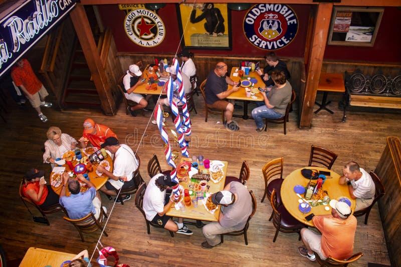 Смотрящ вниз на людях есть, выпивая и проверяя телефоны на баре Joes эскимоса и resturant близко OSU Stillwater Оклахоме США 05 0 стоковые изображения rf