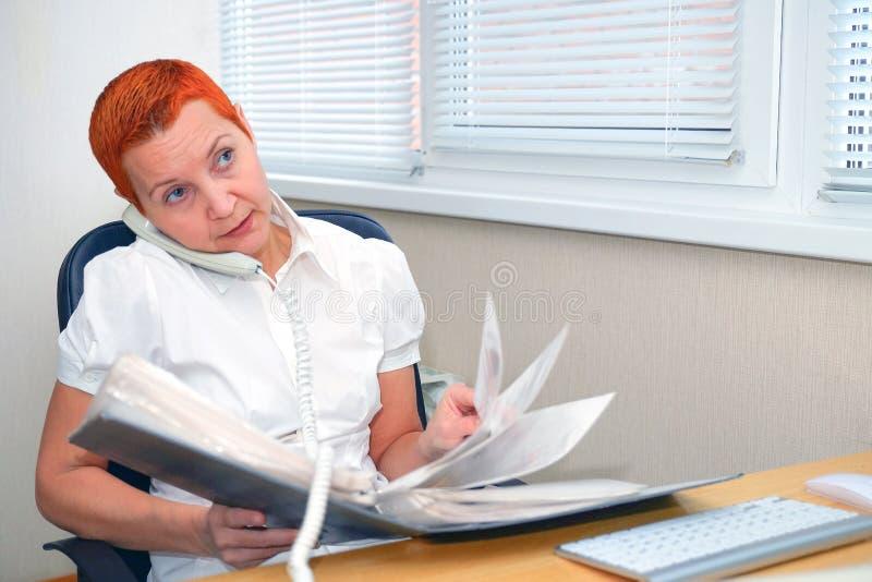 Смотрящ через документы, менеджер офиса девушки говоря по телефону стоковое фото
