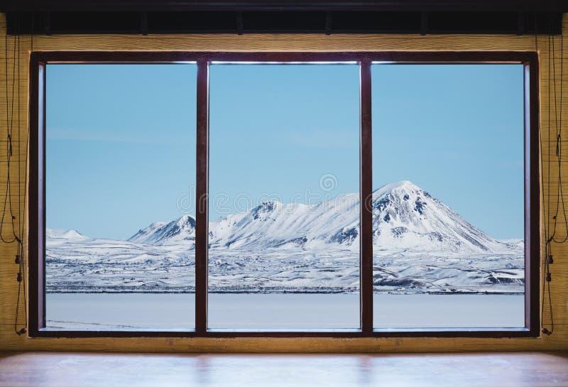 Смотрящ через окно в зиме, деревянную оконную раму с горой снега стола и ландшафта и замороженный вид на озеро в Исландии стоковое фото rf