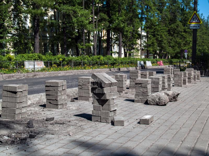 Смотря на плитки для ремонтировать тротуар стоят снаружи в ясном солнечном дне стоковые изображения