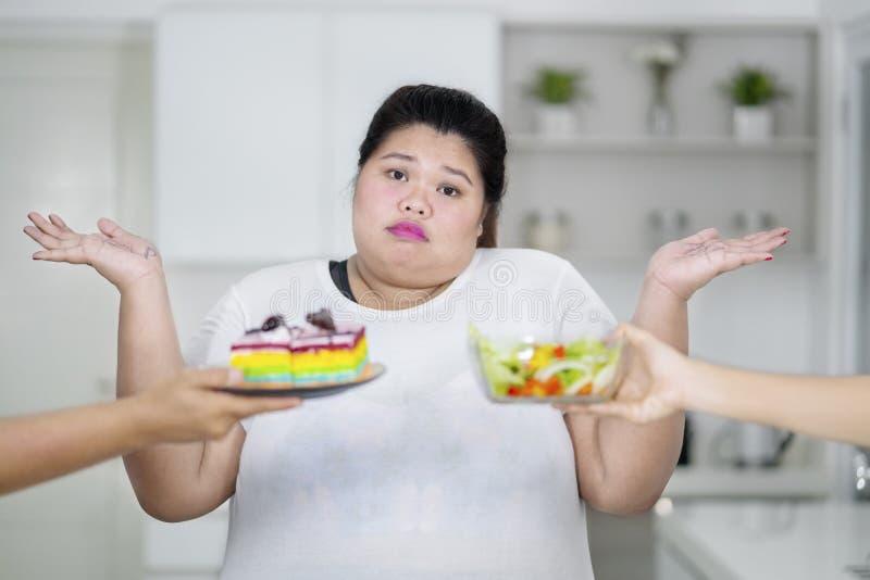 Смутите полную женщину не знает чего выбрать между тортом радуги и салатом стоковые изображения rf