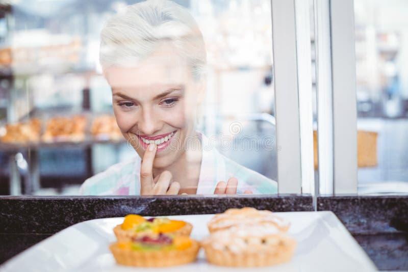 Смущаясь милая женщина смотря пирог плодоовощ стоковая фотография rf