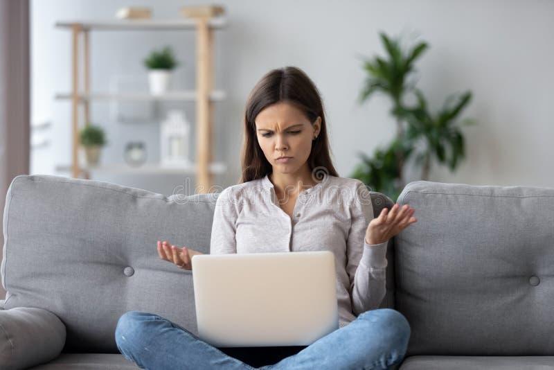 Смущенная молодая женщина смотря на ноутбуке чувствует сбиванной с толку путем читая онлайн новости стоковое изображение