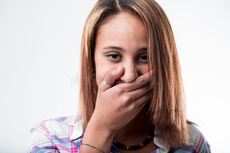 Смущенная молодая женщина покрывая ее рот стоковое изображение