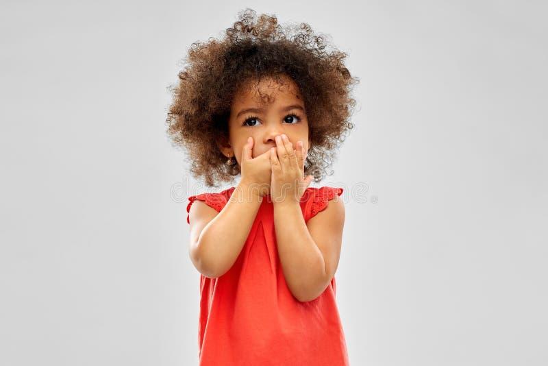 Смущенный Афро-американский рот заволакивания девушки стоковые фотографии rf