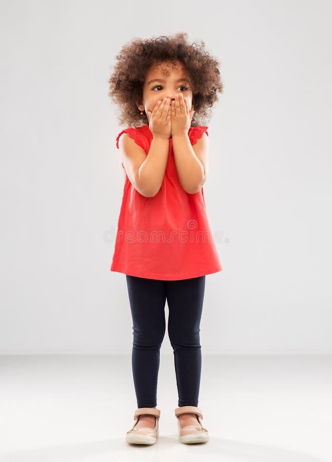 Смущенный Афро-американский рот заволакивания девушки стоковая фотография