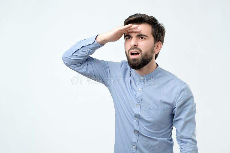 Смущенный молодой испанский человек с бородой смотря далеко стоковое фото