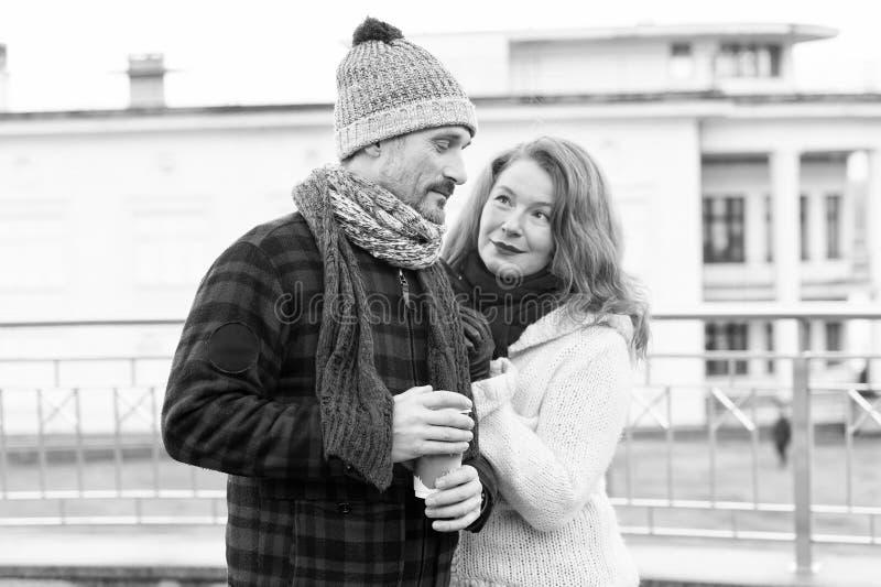 Смущенный парень с кофейной чашкой в руке Достигшие возраста пары встречают на улице Парень женщины довольный о кофе стоковая фотография rf