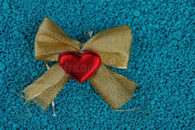 Смычок Брайна и красное сердце на голубых малых камнях стоковые фото