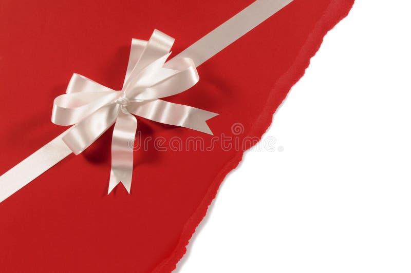 Смычок ленты подарка с untidy сорванной красной бумажной предпосылкой, белым космосом экземпляра стоковое фото rf