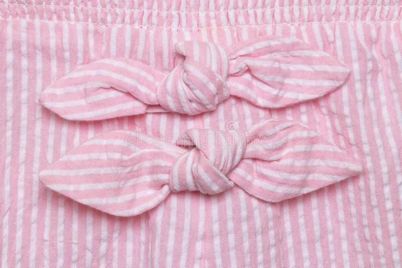 Смычок на платье Детали конца-вверх 2 связей украшения на платье лета пинка белом striped маленькой девочки o стоковые фотографии rf