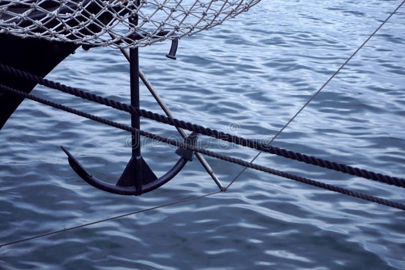 Смычок черной яхты плавания против голубого моря с анкером на смычке скопируйте космос, селективный фокус, узкую глубину поля стоковая фотография rf