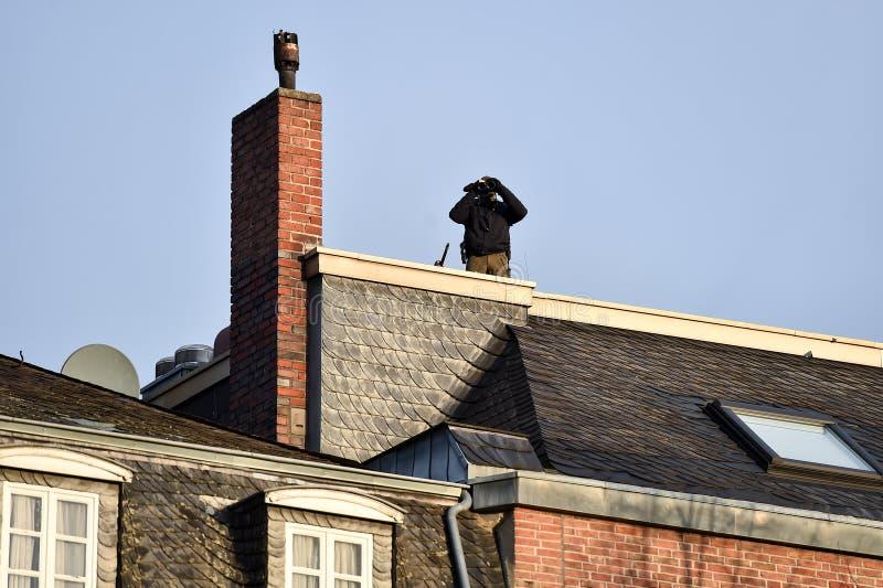 Снайпер обеспечивая периметр от крыши стоковые фотографии rf