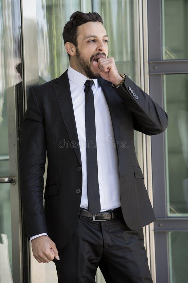 Снаружи красивого бизнесмена стоящее и зевать стоковая фотография