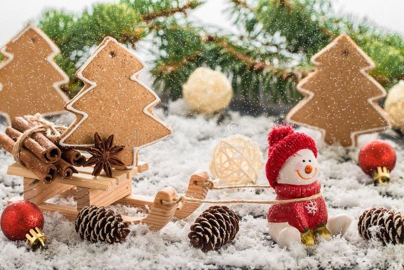 Снеговик в красной крышке на деревянном столе Состав рождества или Нового Года с подарками и печеньями пряника Зимний отдых стоковая фотография rf