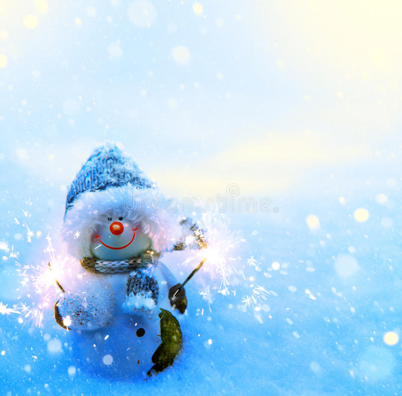 Снеговик и бенгальские огни рождества искусства на голубой предпосылке снега стоковая фотография