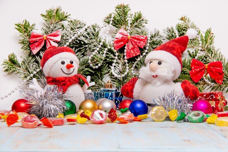 Снеговик и Санта Клаус на предпосылке снег-покрытой рождественской елки с игрушками и конфетой рождества стоковые фото