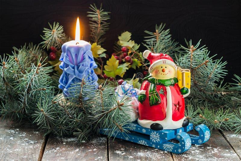 Снеговик и сумка с подарками на скелетоне, свечой в елевом branc стоковые изображения