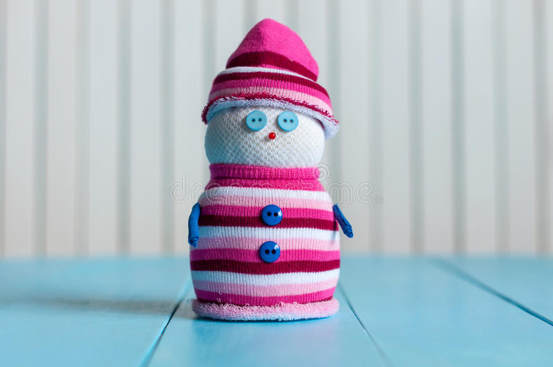 Снеговик нося striped свитер на голубое деревянном стоковое изображение