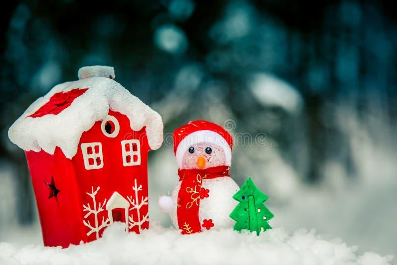 Снеговик состава рождества около красного дома в лесе стоковые фото