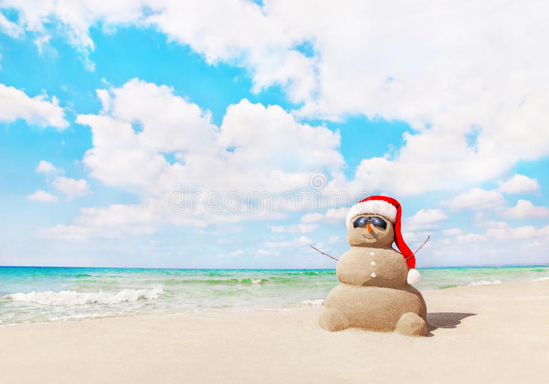 Снеговик Sandy в шляпе santa на пляже моря Новые Годы и рождество стоковое изображение