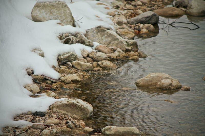 Снег в реке стоковые изображения