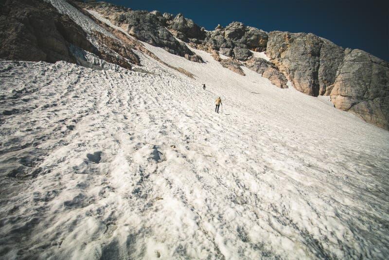 Снег ледника скалистых гор с взбираться путешественников стоковая фотография