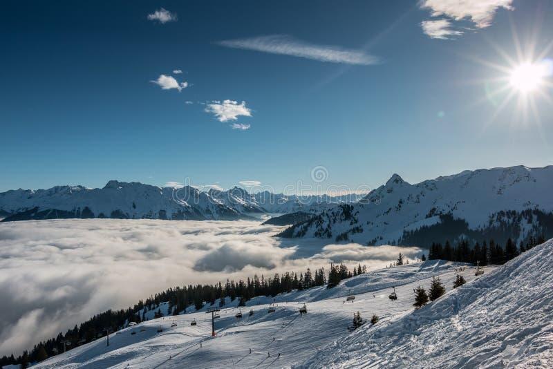 Снег и солнце на верхней части гор и тумана вниз с долины стоковые фотографии rf