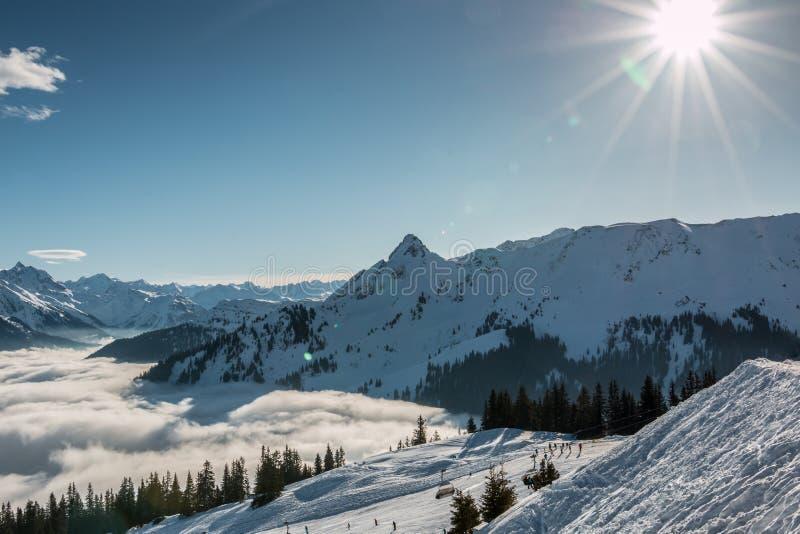 Снег и солнце на верхней части гор и тумана вниз с долины стоковое фото
