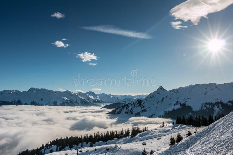 Снег и солнце на верхней части гор и тумана вниз с долины стоковое изображение