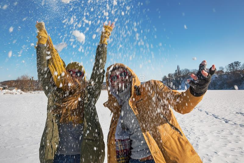 Снег 2 молодых счастливых людей бросая и потеха иметь Селективный f стоковые фотографии rf