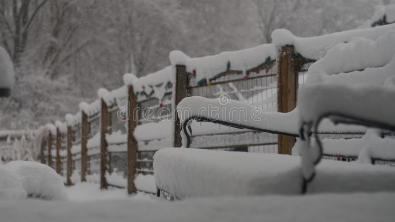 Снег покрыл мебель патио и загородку сада стоковое фото