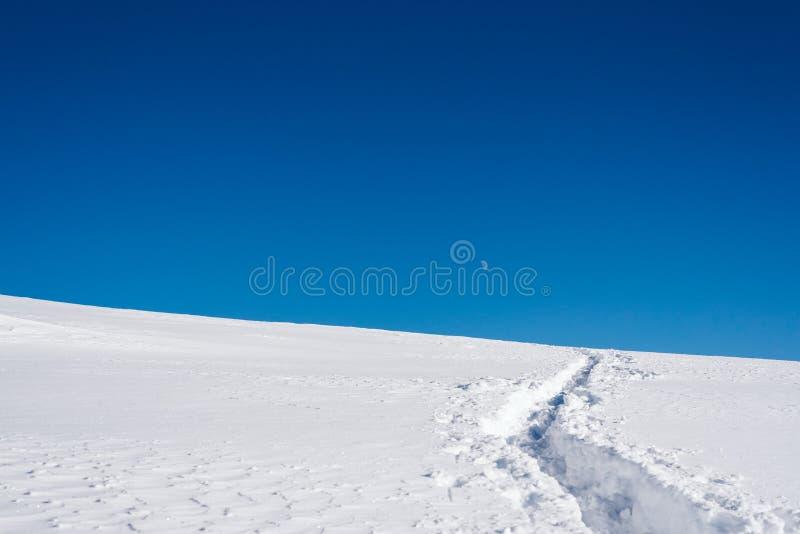 Снег покрыл наклон горы и изумляя голубое небо стоковые фотографии rf