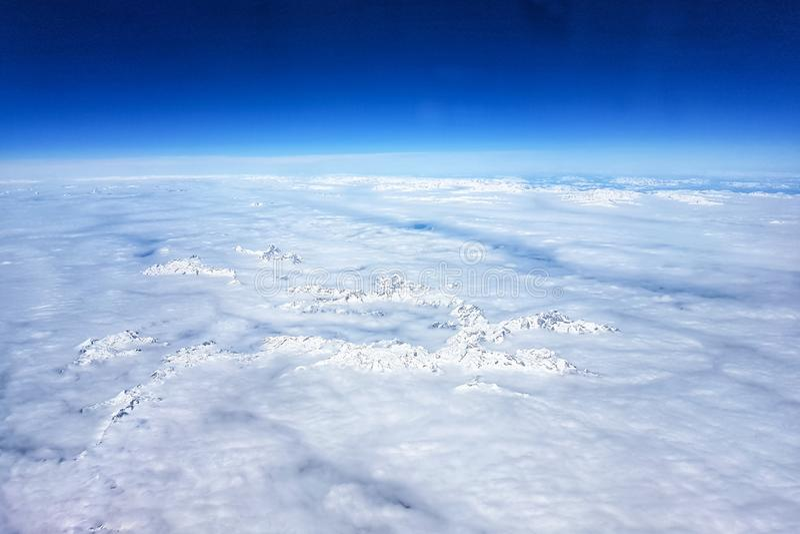 Снег-покрытые горы в облаках, взгляде от самолета стоковое изображение