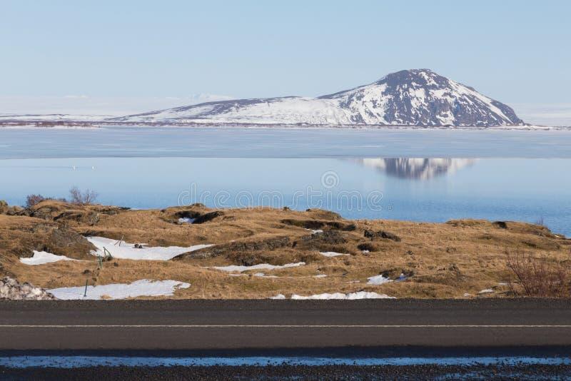 Снег предусматривал гору на естественном озере с ясной предпосылкой голубого неба стоковое фото